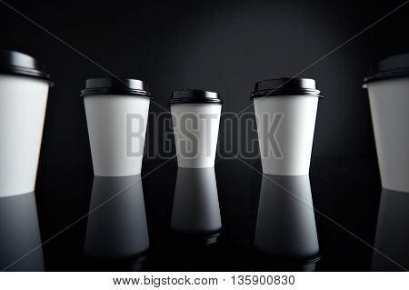 Many white take away paper cups for hot beverages closed with caps presented in perspective, isolated on black and mirrored. Retail mockup presentation