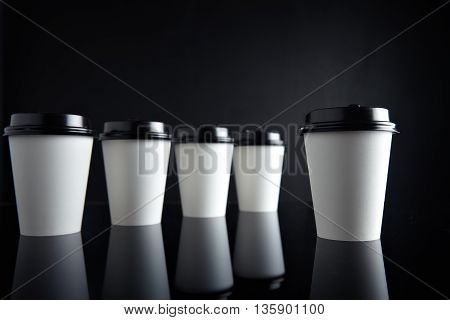 Retail mockup presentation, Luxury set of white take away cardboard paper cups closed with caps isolated on black and mirrored. One cup presented in front