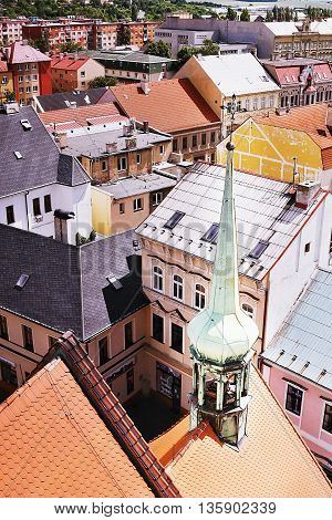 2016/06/18 Chomutov city Czech republic - small green steeple of church 'Kostel Nanebevzetí Panny Marie' with historical houses on background