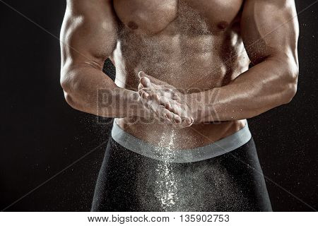 young muscular man preparing to hand lifting heavy weight. White talcum dynamically scatters in different directions. Close-up