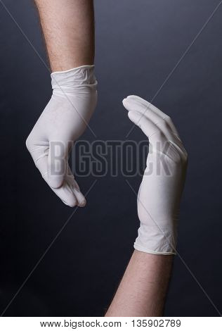 Male hands in latex gloves encircling, holding gesture. Showing or presenting. Dark background. Place for a concept.