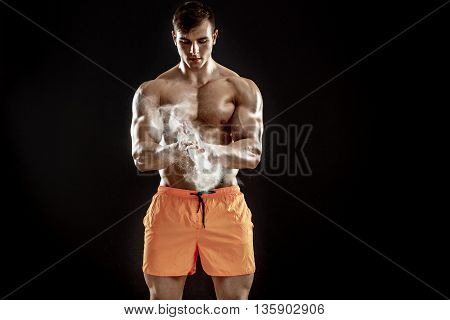 young muscular man preparing to hand lifting heavy weight. White talcum dynamically scatters in different directions