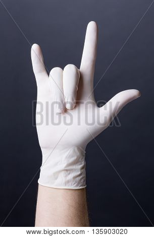 Male hand in latex glove. Doctor or nurse showing a love sign. Dark background