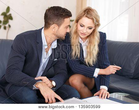 Businesswoman seduce rich businessman on sofa reviewing documents