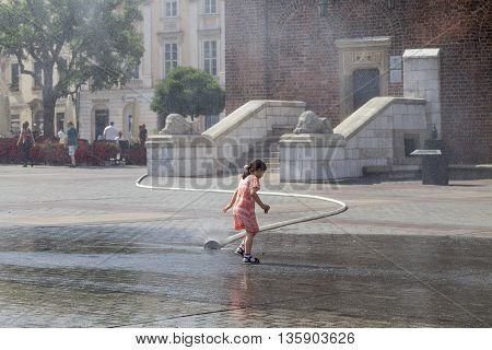 KRAKOW POLAND - June 26 2016 : Small girl using water curtain on main Market Square in sunny day in summer.Curtains are placed by firefighters in the big heat in several places in the city