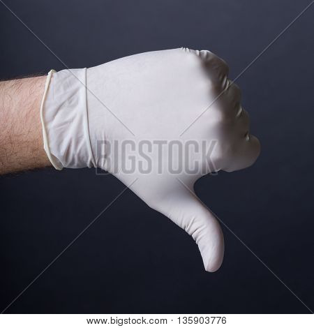 Male hand in latex glove. Thumb down sign. Bad outcome, medical failure, bad healthcare concept. Dark background