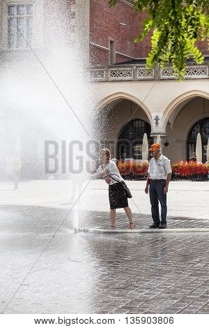 KRAKOW POLAND - June 26 2016 : People using water curtain on main Market Square in sunny hot day in summer.Curtains are placed by firefighters in the big heat in several places in the city