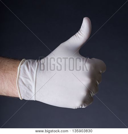Male hand in latex glove. Thumb up sign. Great outcome, success, we will make it concept. Dark background