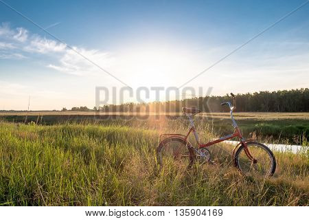 Bicycle In The Field Near The River.