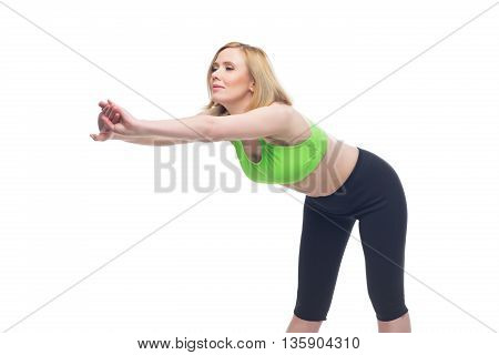 Beautiful middle aged blond fit woman in green bra top and black pants doing sport exercise. Isolated over white background. Copy space.