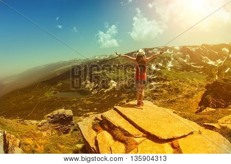Traveler woman relaxing alone Travel Lifestyle concept lake and mountains sunny landscape on background outdoor. Strong tonned photograph.