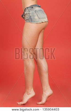 Sexy woman body in jeans shorts. Great ass on red background.