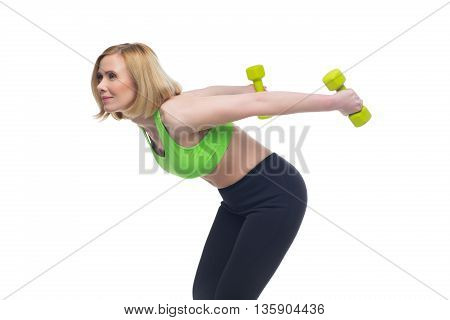 Beautiful middle aged blond fit woman in green bra top and black pants doing sport exercise with dumbbells. Isolated over white background. Copy space.