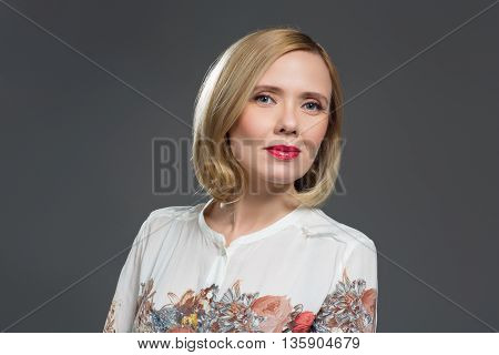 Beautiful middle aged blond woman with makeup over grey background. Copy space.