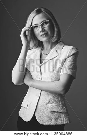 Portrait of elderly business woman in glasses. Happy smiling expression. Over grey background. Copy space. Monochrome.