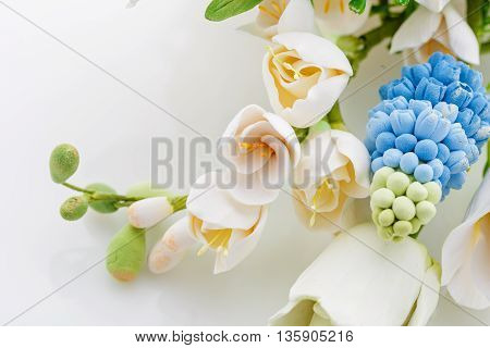 Beautiful handmade art clay spring flower bouquet. Bridal accessory. Over white background. Copuy space.