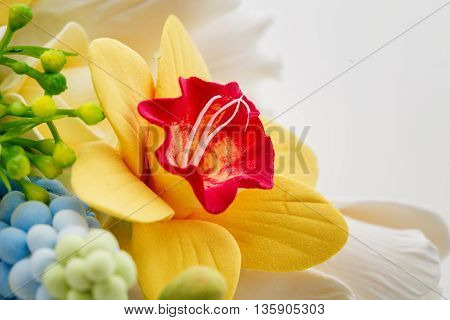 Beautiful handmade art clay spring flower bouquet. Narcissus closeup. Over white background.