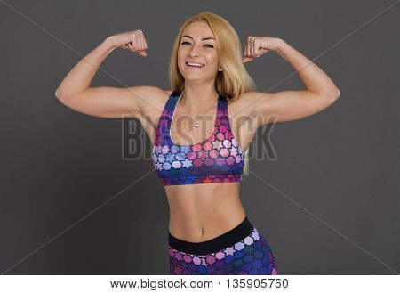 Attractive fit woman exercising in studio . Image of healthy young female athlete doing fitness workout against grey background.