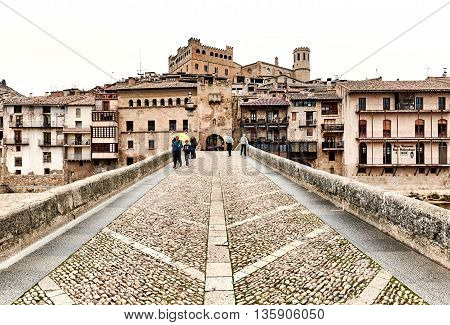 Valderrobres Spain- March 25 2016: Tourists walking across the medieval bridge of San Roque in the Valderrobres village. Valderrobres known as one of the most beautiful village in Spain. Province of Teruel