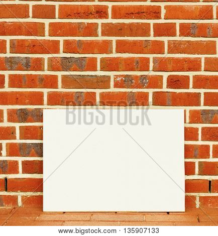 Blank board on a background of a brick wall. Toned image