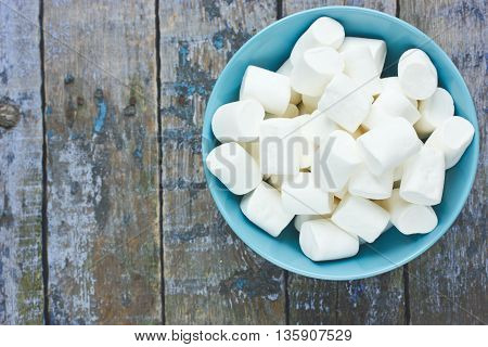 Fluffy white marshmallow in blue bowl on old wooden table top view blank space for text
