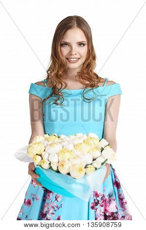 Bouquet of bright paper flowers in a heart-shaped box in the hands of a girl in a bright dress on a white background.