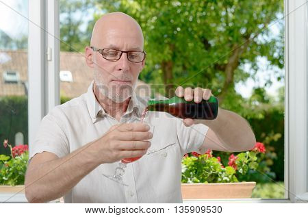 a middle-aged man drinking a glass of beer