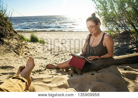 Woman in glasses using digital tablet at sunny sea sand coast. Man feet on foreground. Freelance and rest concept