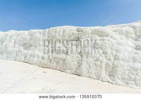 Pamukkale (cotton castle) natural wonder is created by a layers of white travertine looking like cotton, Turkey. Natural pamukkale wall against a blue sky