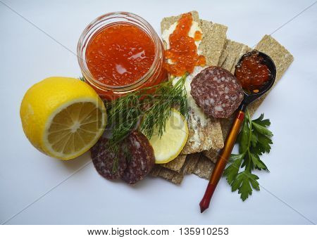 Breakfast of the aristocrat - red caviar, smoked sausage, bread, lemon, greens