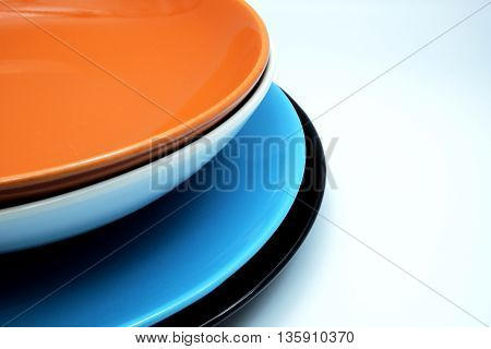 Colorful ceramic plates for the main dishes on blue-white background. Space for texts.