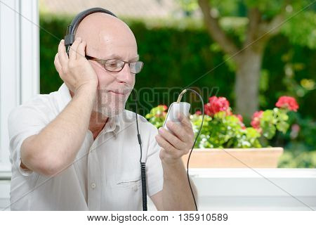 a mature man listening to music with headphones