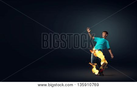Skater boy riding on his skateboard burning in fire