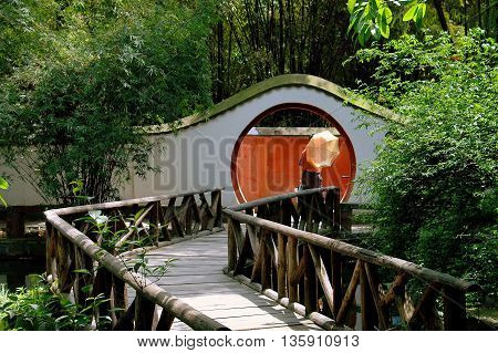 Chengdu China - April 23 2005: A winding wooden bridge leads to a moon gate in the gardens of the Du Fu Thatched Cottage historic site