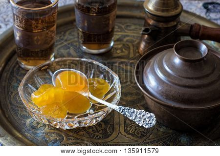 Tea and spoon sweets served on traditional bronze tray