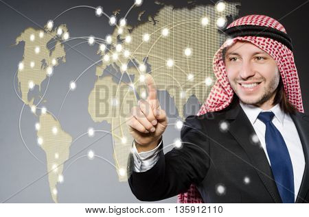 Arab man pressing dots on world map in global communication conc