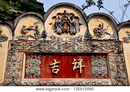 Chengdu China - November 3 2009: 18th century entrance gate panel with hand-painted bas relief designs Chinese characters animals and at the center figures representing long life prosperity and peace on Kuanxiangzi Alley in Old Town