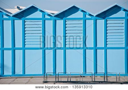 blue cabins on a beach that serve people for undressing