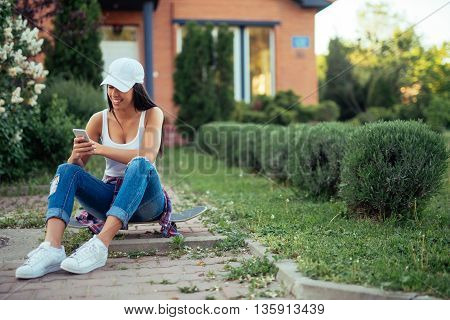 Woman sitting outdoors and surfing the web on a mobile phone.