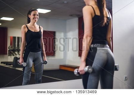 Handsome woman working out with dumbbells in the gym.