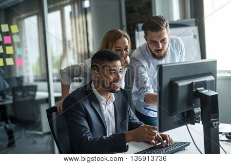 Colleagues working together on a computer in an office.