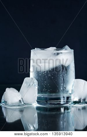 Glass of mineral water near ice cubes on dark background