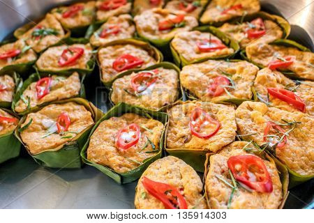 Thai steamed curry fish in banana leaf cups decorated with red chilli (Hor Mok Pla)