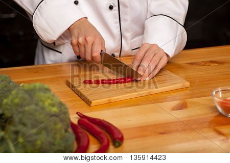 Female Chef Cutting Pepper On Wooden Cutting Board. Broccoli And Pepper On The Table