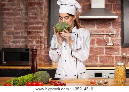 Beautiful Female Cook Smelling Broccoli In The Kitchen
