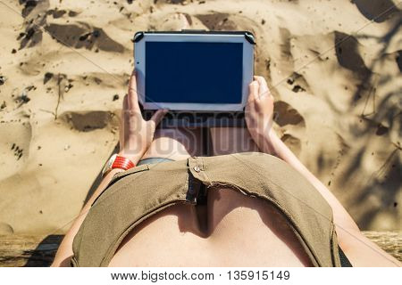 Top view shot of a busty woman holding digital tablet with a blank screen - closeup, fem a hands holding blank digital tablet against sand in sunlight. Focus on beautiful breasts