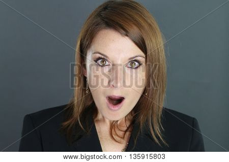 portrait of a surprised woman over a gray background