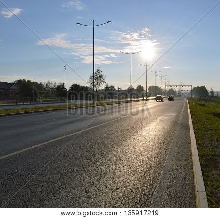 Sunlit automobile city road in th morning