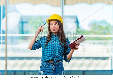 Woman builder taking notes at construction site
