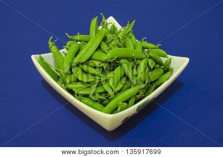 Fresh green peas in white dish on a blue background